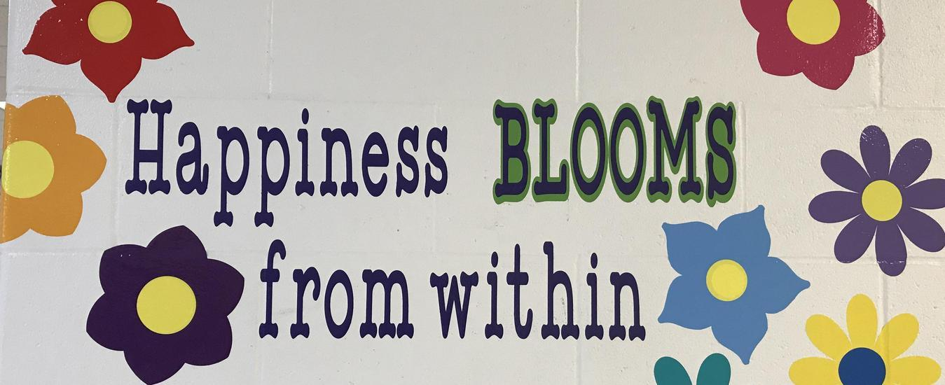 "Mural on wall at Timberlane that says, ""Happiness Blooms from Within"""