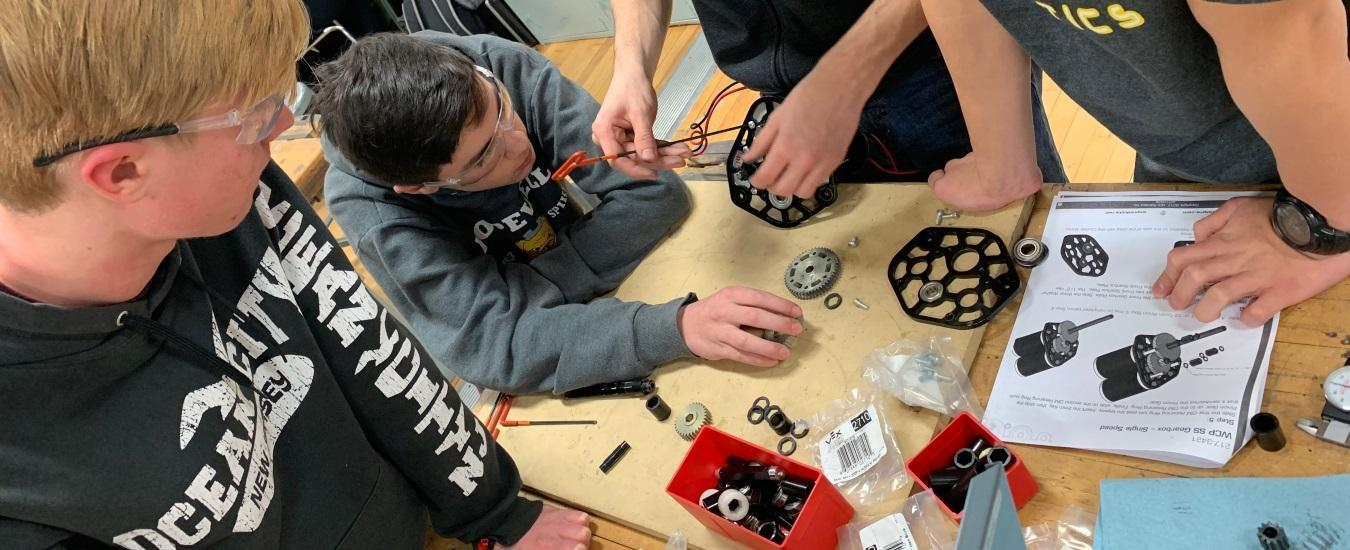 Robotics students assembling gears